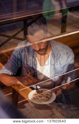 Facing view of hipster man eating pastries in coffee shop