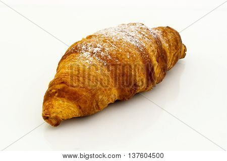 Croissant with powdered sugar on white background.