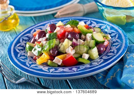 A delicious greek salad with feta cheese kalamata olives cucumber peppers onion and tomato.