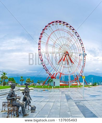 BATUMI GEORGIA - MAY 24 2016: The sculpture group Me You and Batumi with the ferris wheel on the background in the Miracle Park on May 24 in Batumi.