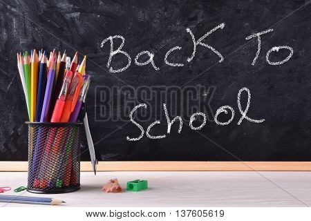 Back To School Written On Blackboard With Container And Pecils