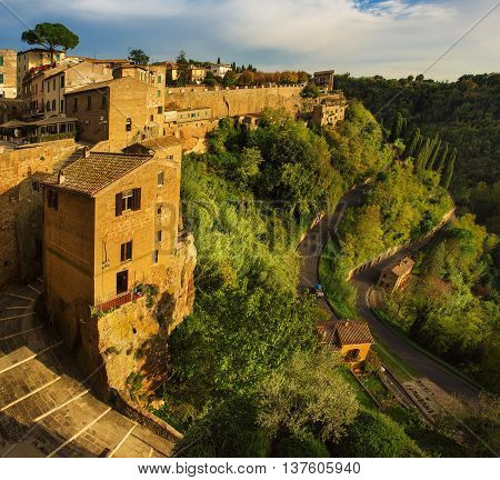 View to the medieval tuff city Pitigliano with green trees and cobblestone stairs, travel Italy vintage  background at sunset