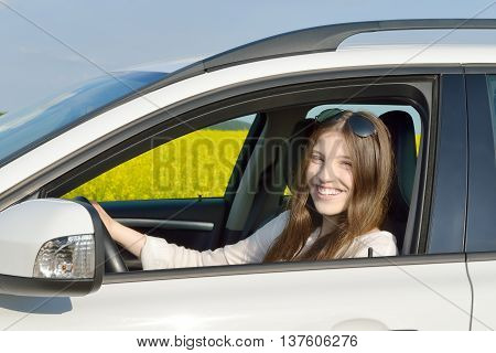 Teen Drivers - Happy teenage female driver sitting in her car which is standing in front of a canola field