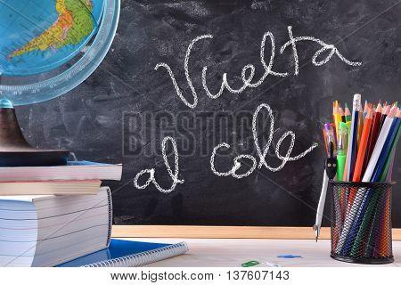 Vuelta Al Cole Written On Blackboard In Center With Tools
