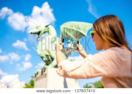 Young female traveler photographing with smart phone Dragon statue on the bridge in Ljubljana city. Dragon statue is one of the most famous symbols of the capital of Slovenia