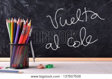 Vuelta Al Cole Written On Blackboard With Container And Pecils