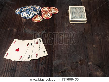Chips and Four aces vintage poker game playing cards on a weathered wood table.