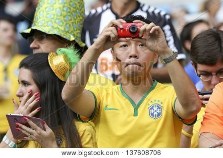 Belo Horizonte Brazil - july 08 2014: Fan with photograph camera during the FIFA 2014 World Cup. Brazil is facing Germany in the semi-finals at Mineirao Stadium