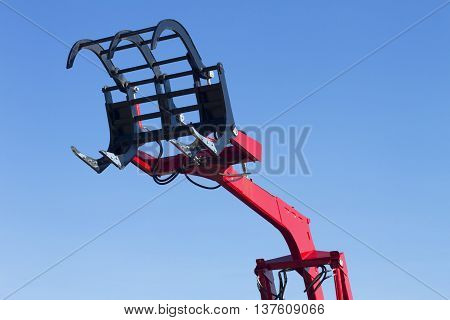 Big red grab of excavator or tractor isolated on white.
