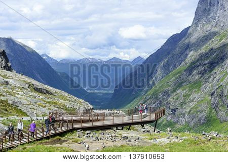 GERANGERFJORD, NORWAY - JUNE 29: Tourists on a viewing platform near the Trollstigen road between the mountains on June 29, 2016 in Geiranger, Norway. Geirangerfjord is UNESCO heritage site.