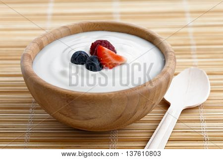 Wooden Bowl Of White Yoghurt On Bamboo Matt With Wooden Spoon. Garnished With Fruit.
