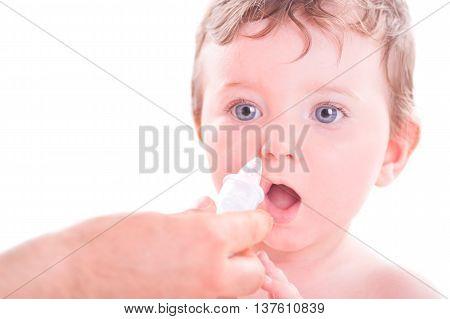 Mother using baby nasal aspirator on her daughter.