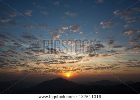 sunrise with scattered clouds sky and the dark mountain foreground
