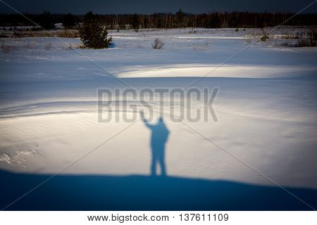 man's shadow on snow surface in winter steppe