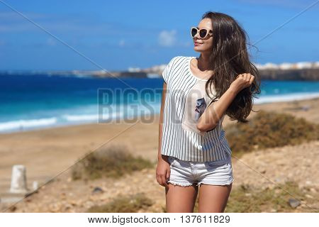 Young beautiful stylish girl posing at beach on a windy day