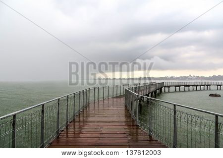 Rain clouds on a bridge going out to sea