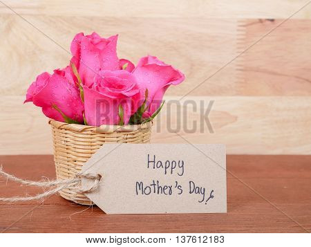 Sweet pink rose flower in the basket and handwriting Happy Mother's Day on brown label paper