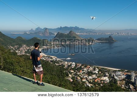 Niteroi, Brazil - July 5, 2016: Young man controlling a drone in Niteroi City Park with a beautiful view of Rio de Janeiro.