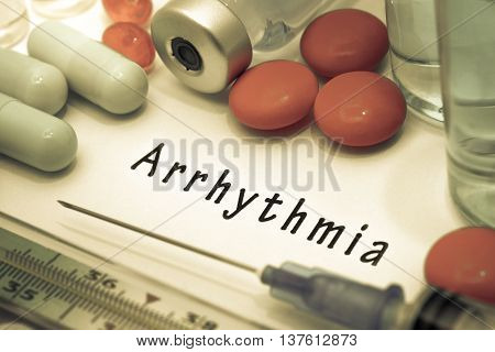 Arrhythmia - diagnosis written on a white piece of paper. Syringe and vaccine with drugs.