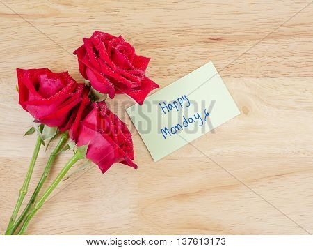 Three red rose flower and handwriting Happy Monday on notepaper with wood background in top view