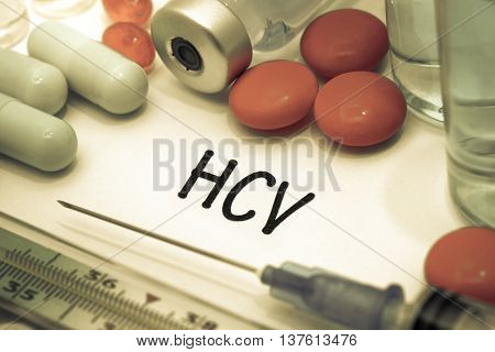 HCV - diagnosis written on a white piece of paper. Syringe and vaccine with drugs.