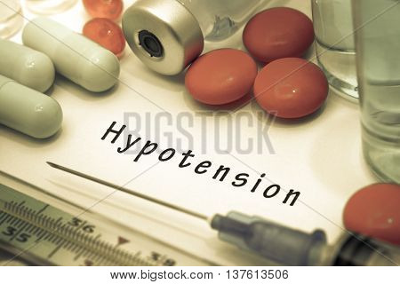 Hypotension - diagnosis written on a white piece of paper. Syringe and vaccine with drugs.