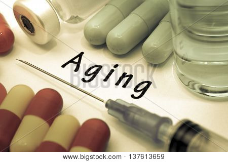 Aging - diagnosis written on a white piece of paper. Syringe and vaccine with drugs