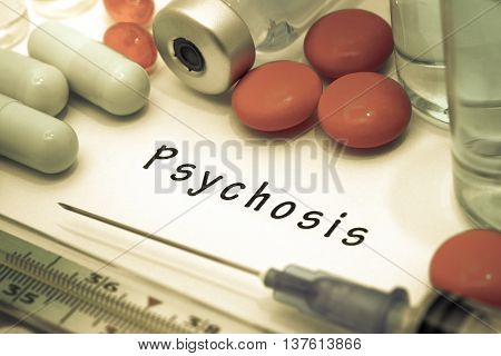 Psychosis - diagnosis written on a white piece of paper. Syringe and vaccine with drugs.