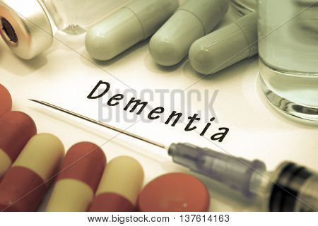 Dementia - diagnosis written on a white piece of paper. Syringe and vaccine with drugs.
