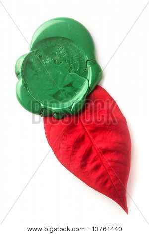 Green wax seal with red leaf isolated on white