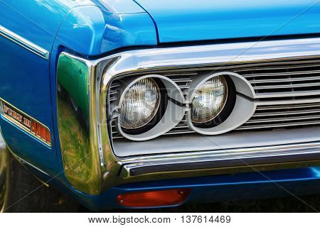 MINSK BELARUS - MAY 07 2016: Close-up photo of the blue Plymouth Fury 3 1972 model year. Headlights of retro car Plymouth Fury III. Selective focus.