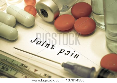 Joint pain - diagnosis written on a white piece of paper. Syringe and vaccine with drugs.