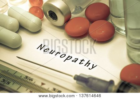 Neuropathy - diagnosis written on a white piece of paper. Syringe and vaccine with drugs.