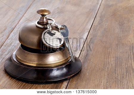 Reception bell and hotel key on a reception desk