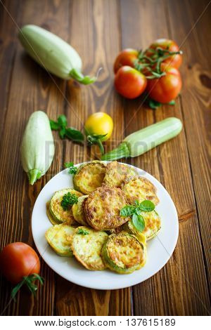 zucchini fried in batter on a wooden table