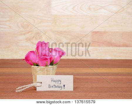 Pink rose flower in the basket and handwriting Happy Birthday on brown label paper with wood background