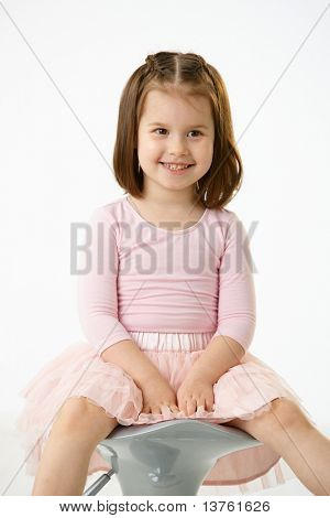 Portrait of happy little girl wearing ballet costume sitting on high chair against white background, smiling.?