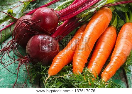A bunch of young organic carrots and beets with leaves on a wooden table. Vegetables from the garden