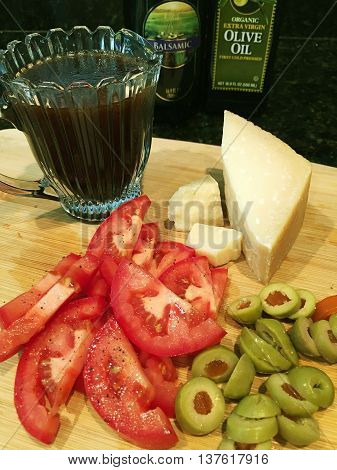 Tomatoes, olives and Parmesan cheese on a cutting board with olive oil and balsamic vinaigrette dressing.
