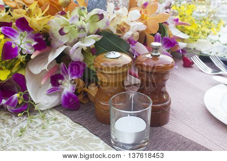 Jars salt and pepper on the table Dinner with flowers.