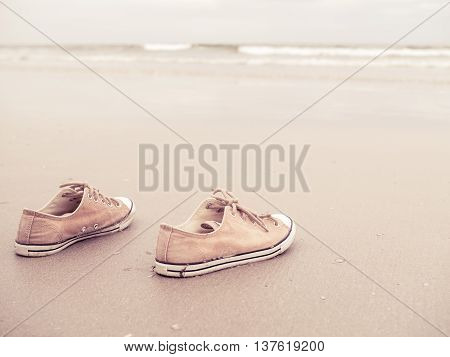 Yellow vintage canvas shoes on the sand beach in vintage filter tone - canvas shoes at the sea beach
