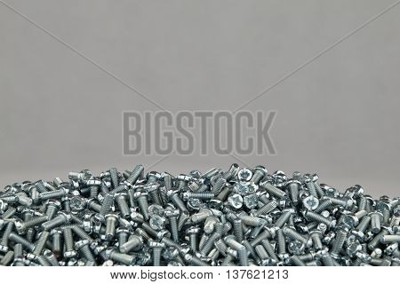 A pile of small screws on a white background.