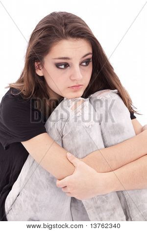 Sad girl teenager sits twining arms about legs
