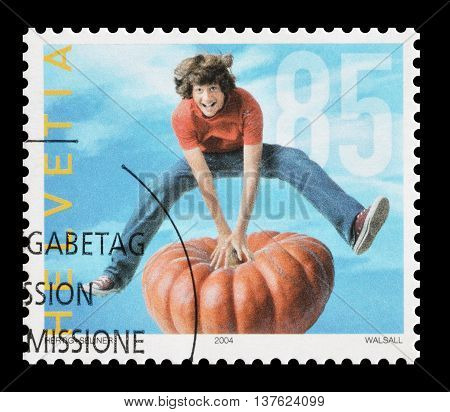 SWITZERLAND - CIRCA 2004 : Cancelled postage stamp printed by Switzerland, that shows teenager jumping over pumpkin.