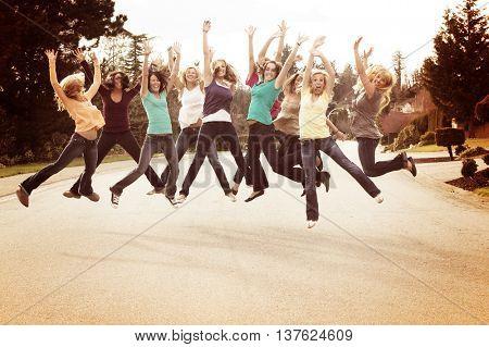 Ten beautiful girls, outside jumping for joy.