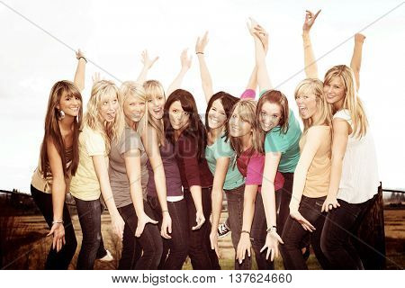 Ten smiling happy teenage girls outside with arms stretched.