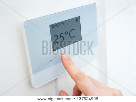 Heating Concept. Hand Is Adjusting Temperature In Room On Digita
