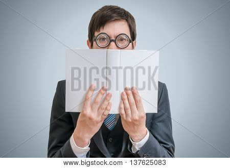 Young Shy Man Is Reading And Is Hiding His Face Behind Book With