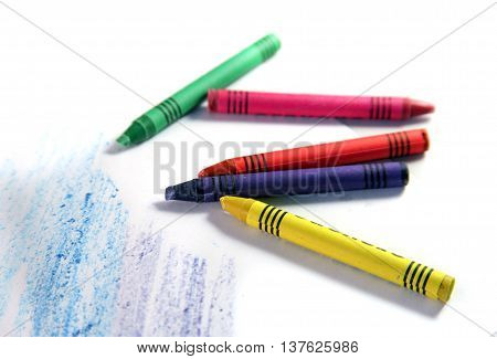 Set of multi-colored wax crayons with drawing stripes on a white background. Creation