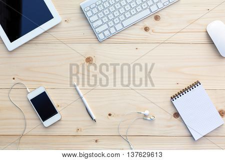 Light wooden Background and modern Business Items on Desk Office Computer Keyboard and Mouse White Pen Tablet PC opened Notepad Earphones dynamic Diagonal alignment